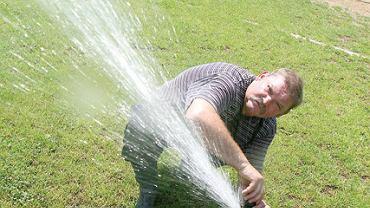 Są różne sposoby na nawadnianie boiska... 19 czerwca 2008, godz. 11.45 Czernichów. Stanisław Nowak rozkłada zraszacze na boisku LKS-u Czernichów Magurka.