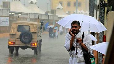 Muzułmanin odbywający hadżdż rozmawia przez telefon na ulicy Mekki.