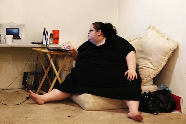 Donna Simpson uses a computer to check a site that pays her money to upload video clips of her eating at her home in Old Bridge, New Jersey June 8, 2010. Simpson, 42, who weighs more than 600 pounds (272 kg) and aims to reach 1,000 pounds (455 kg), is waging a campaign to become the world's heaviest living woman, admitting that she is as hungry for attention as she is for calorie-rich food. Picture taken June 8, 2010. REUTERS/Lucas Jackson (UNITED STATES - Tags: HEALTH SOCIETY)