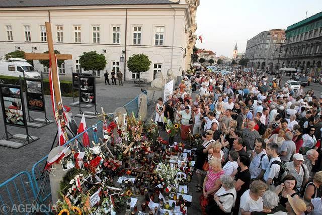 Ludzie modlący się pod krzyżem przed Pałacem Prezydenckim