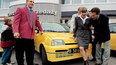 1996. Trójka złotych medalistów z Atlanty: Ryszard Wolny, Renata Mauer i Robert Korzeniowski odbierają w Bielsku cinquecento. Nagrodę ufundował Fiat, który był sponsorem polskiej reprezentacji. Cztery lata później, w 2000 roku, złoci medaliści z Sydney odbierali seicento, tylko Robert Korzeniowski, który zdobył wtedy dwa złote medale, zamienił dwa małe samochody na fiata mareę. Tego samego roku w ramach kontraktu z Fiatem PKOl dostał dla najwyższych urzędników pięć luksusowych samochodów. Medalistom musiały wystarczyć seicento