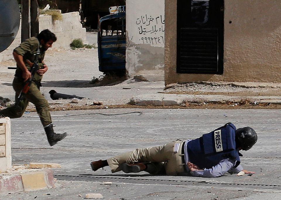 Reporter AFP Sammy Ketz leży na ziemi podczas ostrzału przez snajperów w syryjskim mieście Maalula, 18 września 2013 r.