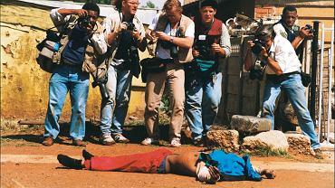 Grupa fotoreporterów stoi nad ciałem zabitego mężczyzny. Fotografują zwłoki jednego z ludzi, którzy zginęli podczas zamieszek przed pierwszymi wolnymi wyborami w RPA w 1994 roku. Krzysztof Miller nie pokazuje samej ofiary. Skupia się na sytuacji, sam ukryty za kadrem uwiecznia pracę swoich kolegów. Tak powstaje jedno z najsłynniejszych jego zdjęć, często przywoływane jako ilustracja reporterskiej pogoni za sensacją i śmiercią