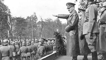 27 września 1939 r. nad ranem nastąpiło zawieszenie broni, wszystko ucichło, a na zasypane gruzem ulice ludzie wychodzili z piwnic. W mieście wybite były niemal wszystkie szyby, w wielu miejscach leżały martwe konie zabite wybuchami lub odłamkami. Głodujący mieszkańcy natychmiast rozbierali ich mięso. 28 września na zajmowanym przez Niemców Okęciu w fabryce zakładów Škoda w alei Krakowskiej (dziś to część hal PZL Okęcie) podpisana została kapitulacja. Ze strony polskiej podpis złożył gen. Tadeusz Kutrzeba, z niemieckiej gen. Johannes Blaskowitz. Na zdjęciu Adolf Hitler przyjmuje defiladę wojsk niemieckich w Alejach Ujazdowskich w Warszawie. Widoczni także gen. Gunther von Kluge (drugi z lewej), gen. Maximilian von Weichs (w hełmie), gen. Fedor von Bock (drugi z prawej), 5 października 1939 r.
