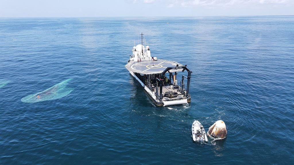 Przygotowania do podjęcia statku Crew Dragon z wody. Po lewej widać odczepione spadochrony. Załoga po wstępnym badaniu medycznym jest wysyłana na brzeg śmigłowcem