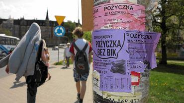 Ogłoszenie o pożyczkach naklejone na słupie w Olsztynie.