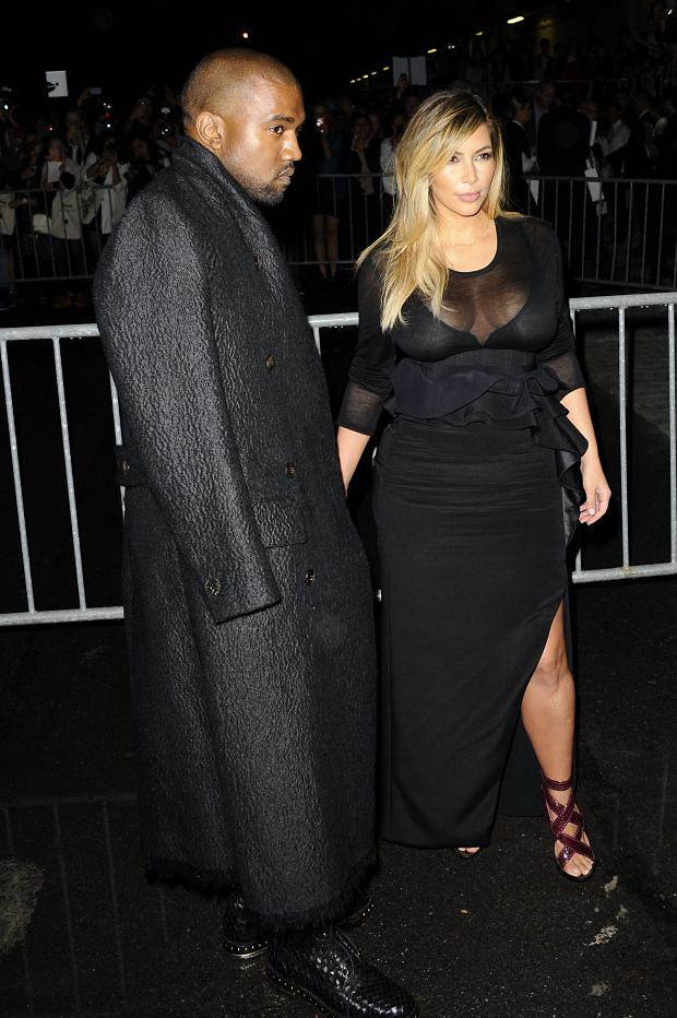 Kanye West, left, and Kim Kardashian arrive to attend Givenchy's ready-to-wear Spring/Summer 2014 fashion collection, presented Sunday, Sept. 29, 2013 in Paris. (AP Photo/Zacharie Scheurer)