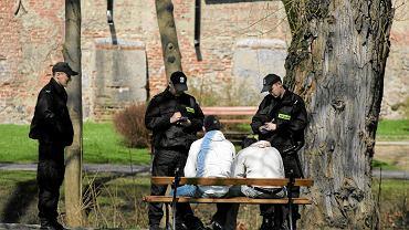 Policjanci spisują mężczyzn pijących alkohol w parku Podzamcze w Olsztynie