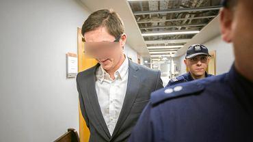 Adwokat Jakub Brykczyński prowadzony na salę rozpraw w poznańskim sądzie. Po prawomocnym wyroku mamy prawo publikować dane osobowe, ale nie obejmuje to wizerunku skazanego