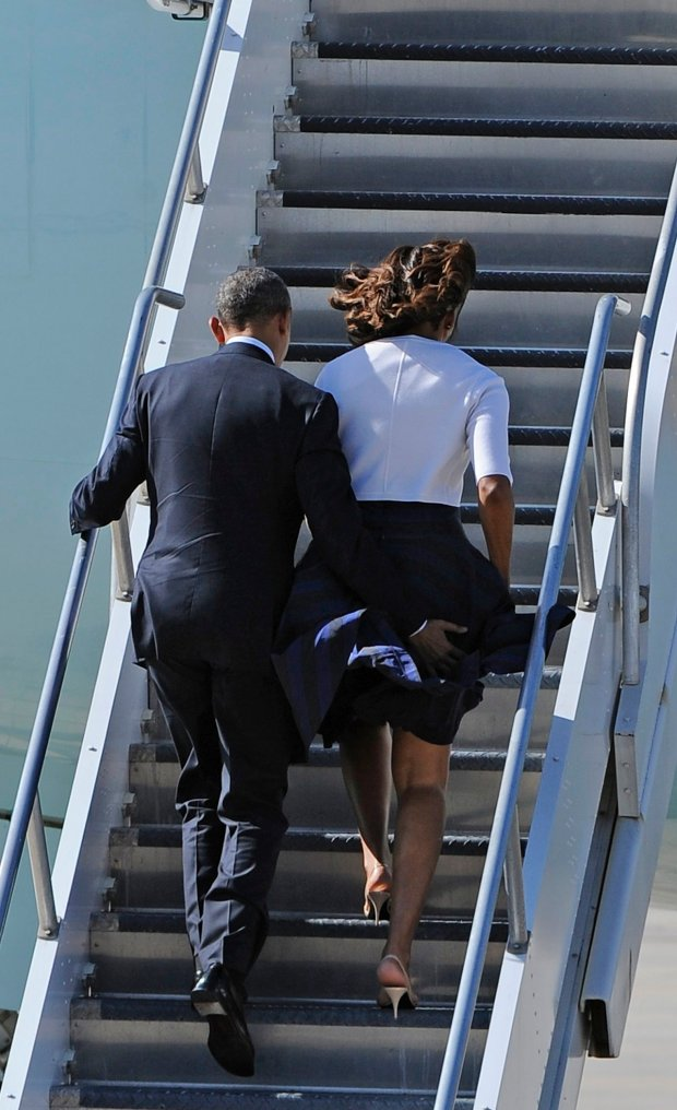 President Barack Obama helps his wife, first lady Michelle Obama keep her skirt from blowing as they board Air Force One, Thursday, April 10, 2014, in Houston. The president and first lady are headed to Austin for a 50th anniversary summit for the signing of the Civil Rights Act. (AP Photo/Pat Sullivan)