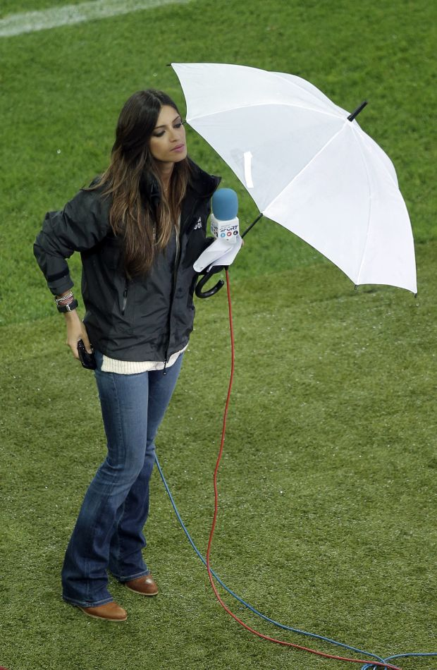 Spanish TV host Sara Carbonero holds an umbrella prior to the Euro 2012 soccer championship Group C match between Spain and Ireland in Gdansk, Poland, Thursday, June 14, 2012. (AP Photo/Gero Breloer)