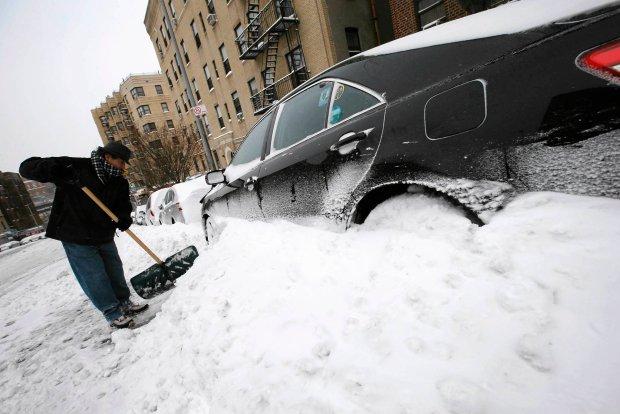 Carlos Mendez odśnieża swój samochód w południowym Bronxie w Nowym Jorku