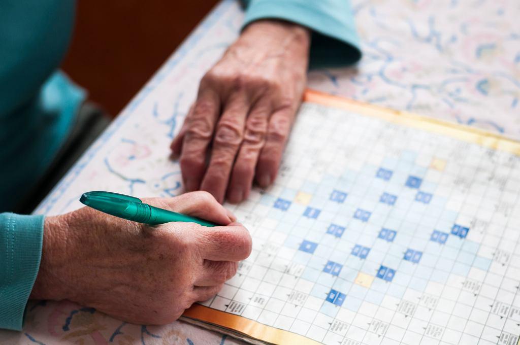 Starsza kobieta rozwiązuje krzyżówkę
