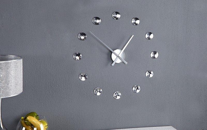 Zegar ścienny z kryształkami prezentuje się świetnie na szarej, surowej ścianie.