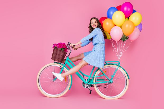 Full length body size profile side view of attractive cheerful cheery wavy-haired lady riding bike without legs delivering decoration event having fun isolated pink pastel color background