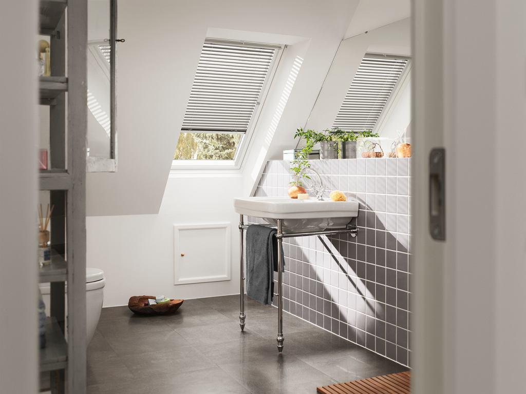 Umywalka przy oknie w łazience na poddaszu