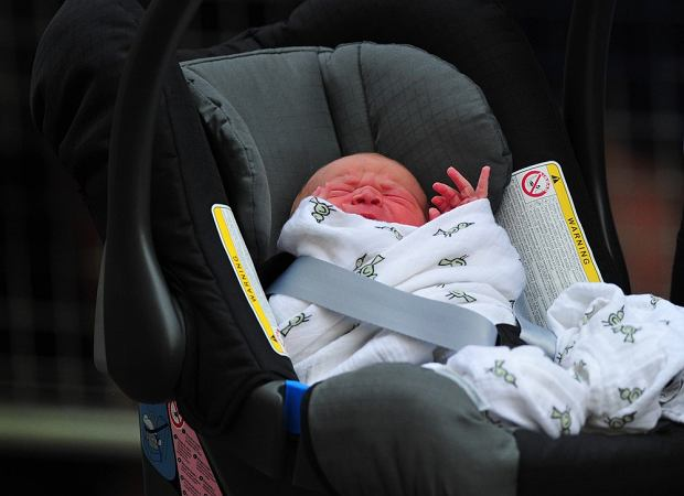 Prince William and Catherine, Duchess of Cambridge' new-born baby boy seen in a car seat outside the Lindo Wing of St Mary's Hospital in London on July 23, 2013. The baby was born on Monday afternoon weighing eight pounds six ounces (3.8 kilogrammes). The baby, titled His Royal Highness, Prince (name) of Cambridge, is directly in line to inherit the throne after Charles, Queen Elizabeth II's eldest son and heir, and his eldest son William.  AFP PHOTO / CARL COURT