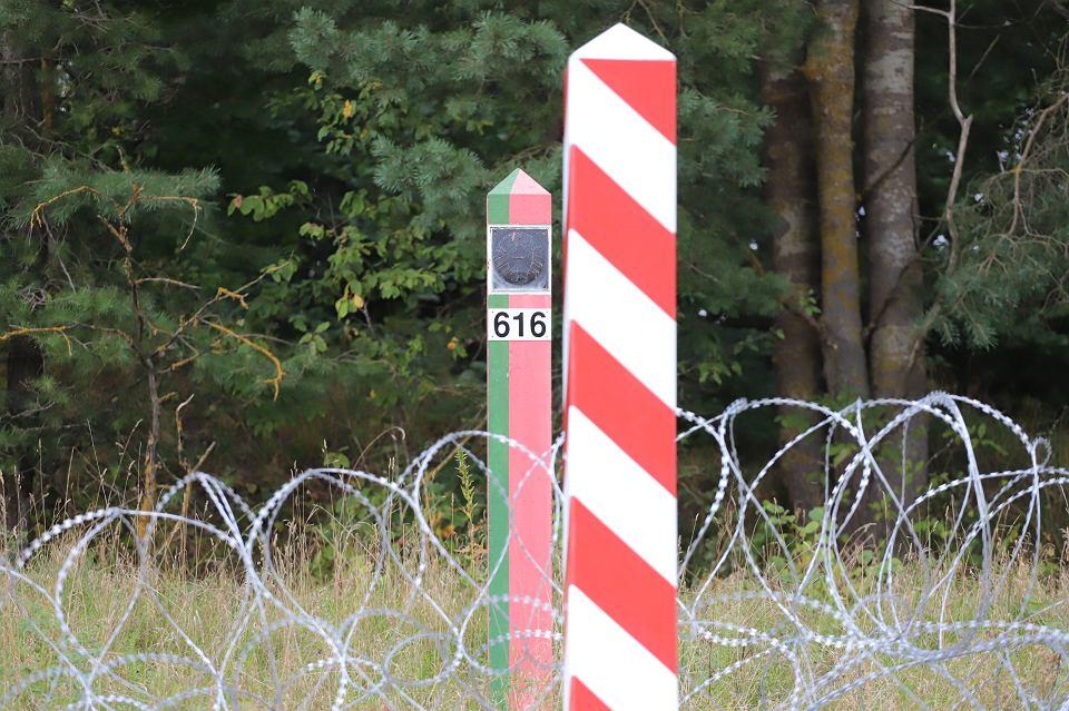 Kopczany. Mariusz Błaszczak, minister obrony narodowej, w poniedziałek (23 sierpnia) zapowiedział powstanie na granicy z Białorusią 'nowego, solidnego płotu' o wysokości 2,5 m. W trakcie konferencji prasowej na granicy polsko-białoruskiej w pobliżu Litwy oświadczył na tle zasieków i w otoczeniu kordonu żołnierzy z karabinami: - Nie pozwolimy na forsowanie granicy. Na zdjęciu słup graniczny i zasieki z drutu falanga rozciągniętego wzdłuż granicy