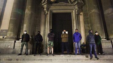 Grupa mężczyzn przed kościołem św. Anny w Krakowie podczas wieczornego marszu Strajku Kobiet