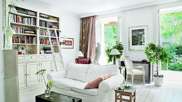 Cały w bieli. W salonie jasne są nie tylko meble (kanapa z IKEA, fotel z BBHome, biblioteczka zrobiona na zamówienie), ale i modrzewiowe deski na podłodze - kiedyś... pomarańczowe. Nad biurkiem obraz Jana Tarasina.