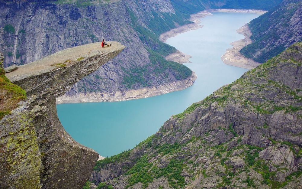 Duże, otwarte przestrzenie u niektórych mogą wywoływać lęki, które nawet mają swoją fachową nazwę: agorafobia, ale innym dostarczają mnóstwa niezapomnianych wrażeń. Prezentujemy Wam miejsca, w obliczu których poczujecie się małą, maleńką kropką na mapie. // NORWEGIA. Język Trolla - Trolltunga. Ta niesamowita skalna półka nad norweskim fiordem Sorifjorden (odnoga Hardanger) wzbudza emocje i pozwala napawać się wspaniałymi widokami, ale każdy, kto cierpi na lęk wysokości, powinien omijać ją szerokim łukiem - skała wisi 700 metrów na jeziorem zatokowym, a jej krawędzie są niezabezpieczone.