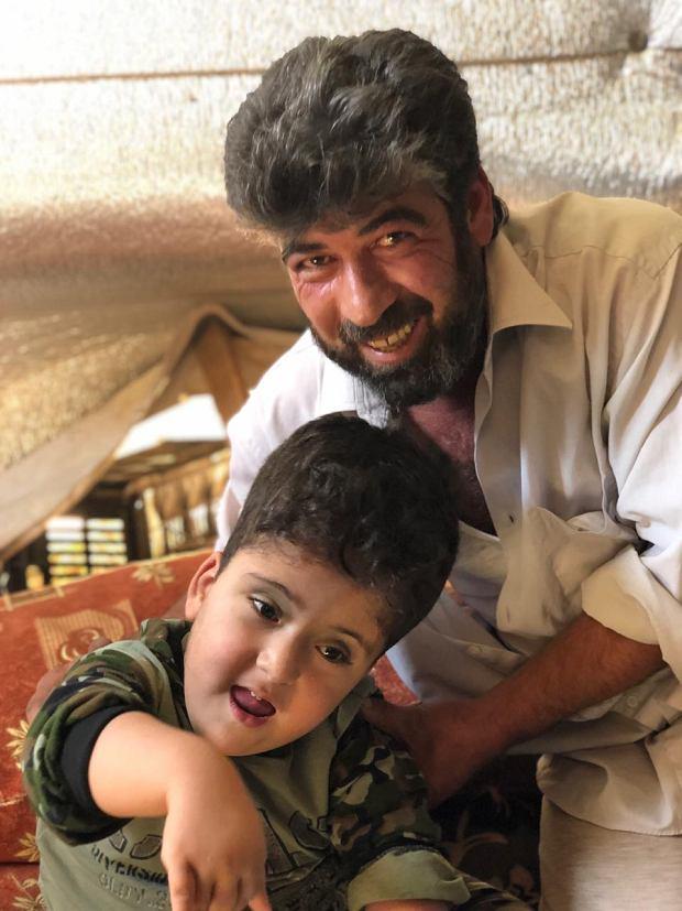 Maher to czteroletni niepełnosprawny syryjski uchodźca. 'Jest naszym źródłem radości' - mówi o nim rodzina. Na zdjęciu Maher z tatą