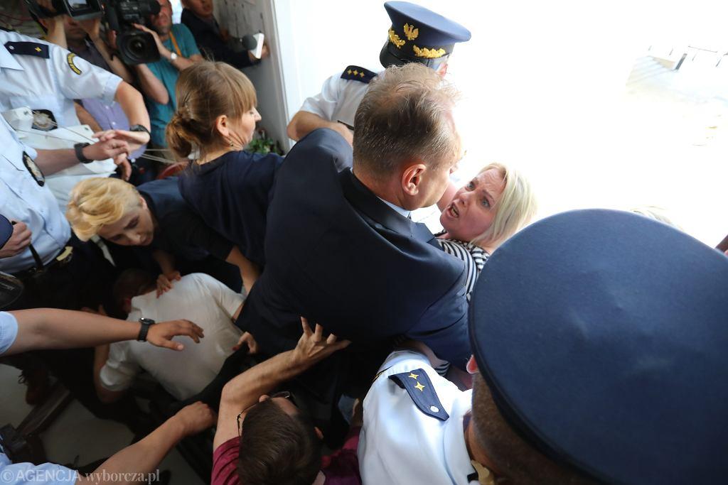 Interwencja Straży Marszałkowskiej gdy protestujący chcieli wywiesić transparent w języku angielskim. Mężczyzna w garniturze to Krzysztof Pręgowski