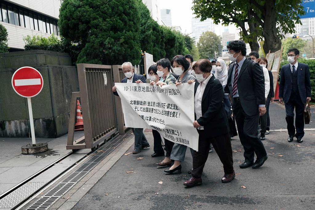 Pięć osób domaga się od Korei Północnej zadośćuczynienia za udział w programie repatriacyjnym. Napis: '14 października w Sądzie Okręgowym w Tokio ruszył pierwszy proces w kampanii Korea Północna 'rajem na Ziemi''