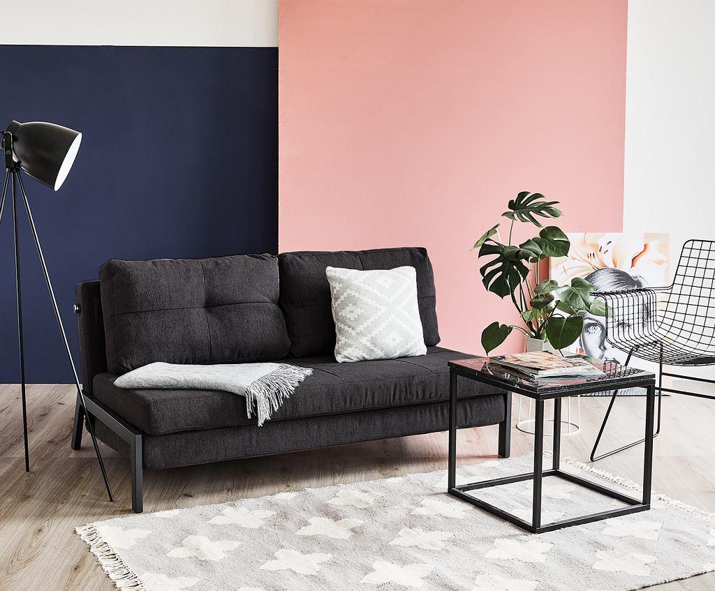 Grafitowa sofa rozkładana na tle barwnej ściany