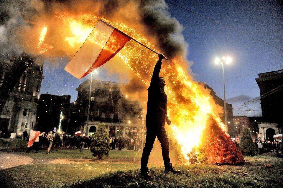 Demonstrant z polską flagą na pl. Zbawiciela. W tle płonąca tęcza. Ponad 1000 osób opublikowało to zdjęcie na Facebooku. Zarówno ci oburzeni spaleniem tęczy na pl. Zbawiciela, jak i fani profilu