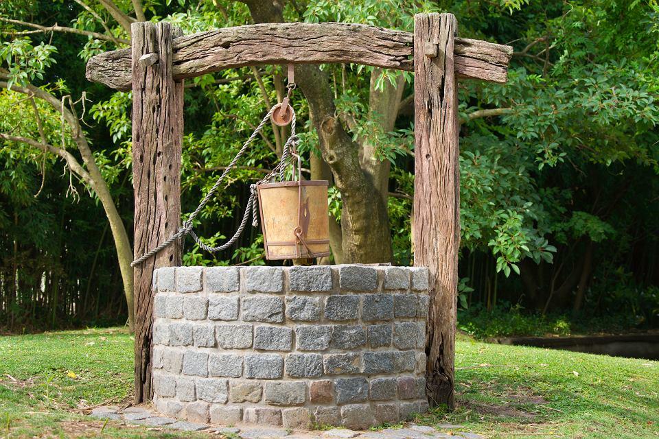Studnia ozdobiona naturalnym kamieniem i starym drewnem.