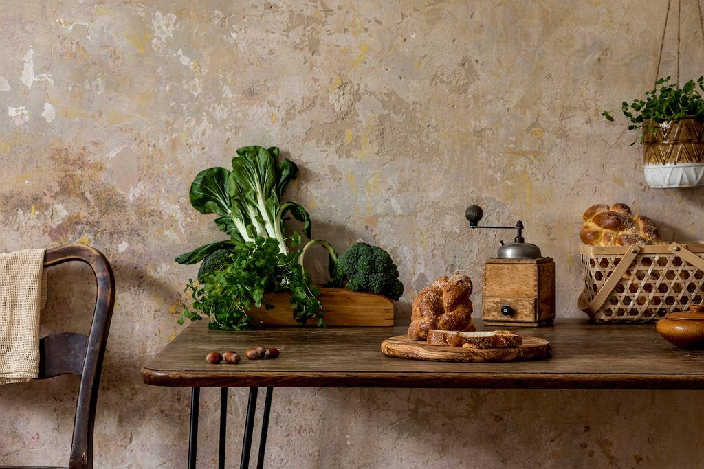 Kuchnia z niewielkim stołem, na którym znajdują się zielone warzywa i chałka.