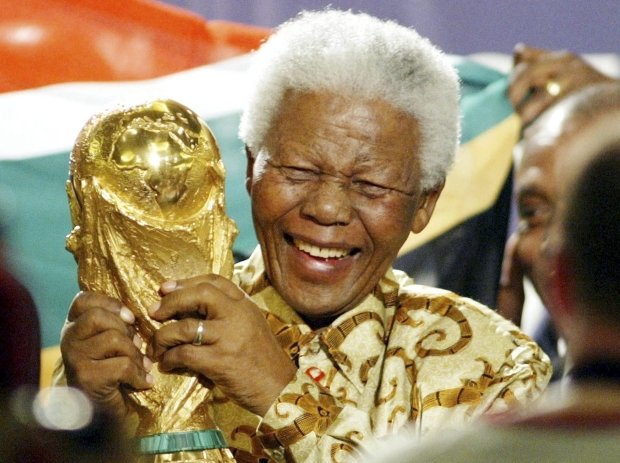 FILE - In this May 15, 2004 file photo, former South African President Nelson Mandela lifts the World Cup trophy in Zurich, Switzerland, after FIFAs executive committee announced that South Africa would host the 2010 FIFA World Cup soccer tournament. Mandela was pivotal in helping the country win the right to host the tournament. South Africas President Jacob Zuma said, Thursday, Dec. 5, 2013, that Mandela has died. He was 95. (AP Photo/Michael Probst, File)