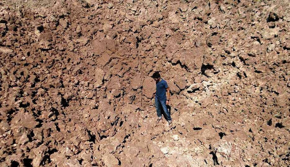 Mieszkaniec Syrii w leju po bombie po ataku lotniczym na miejscowość Sarakeb w północno-zachodniej części kraju