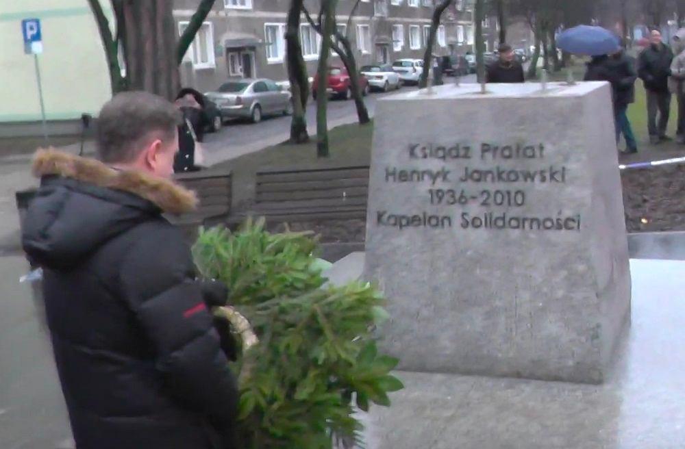 Piotr Duda przed cokołem pomnika ks. Henryka Jankowskiego w Gdańsku