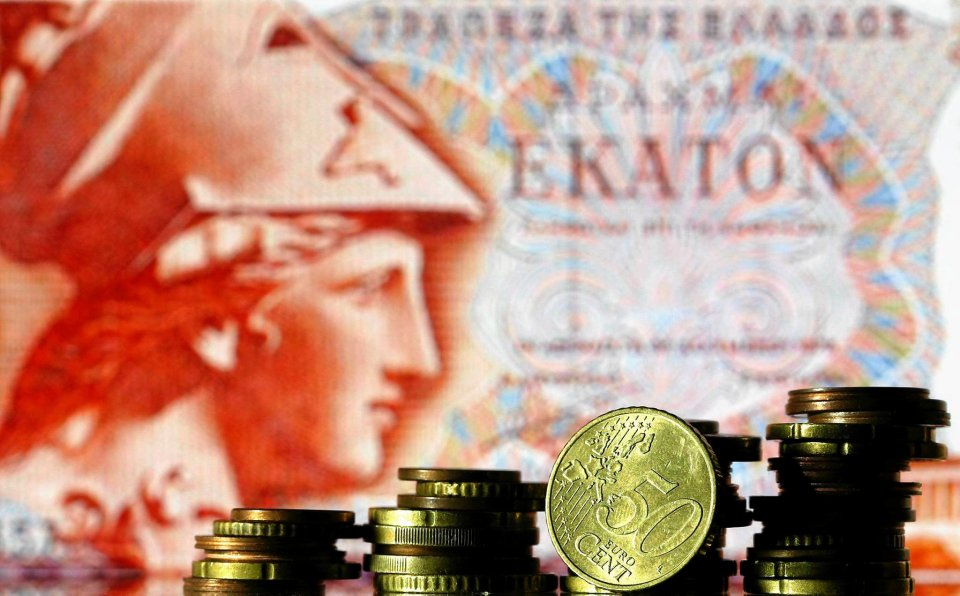 Moneta euro na tle starego banknotu o nominale 100 drachm.