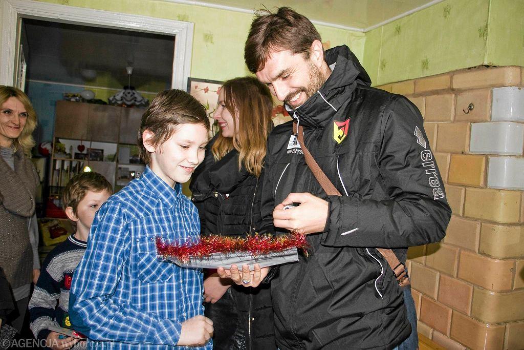 Finał akcji 'Szlachetna Paczka'. Pilkarz Jagiellonii Sebastian Madera przekazuje prezenty Annie Klepackiej i jej synom: Danielowi i Damianowi.