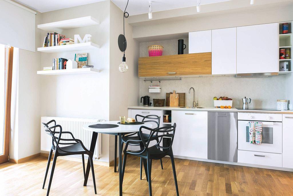 Aneks kuchenny znajduje się w salonie wzdłuż jednej ściany. Zabudowa kuchenna jest nieregularna, co dodaje wrażenia dynamizmu.