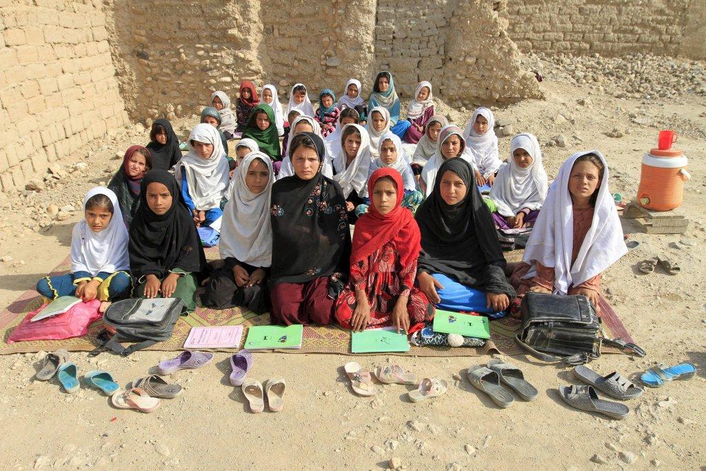 Nauczycielka Mahajera Armani pozuje wraz z żeńską klasą na otwartym terenie szkoły w Jalalabadzie, w Afganistanie. Edukacja w Afganistanie jest obowiązkowa od 6-tego do 18-ego roku życia. Obejmuje 6 klas szkoły podstawowej, 3 klasy gimnazjum i 3 klasy szkoły zawodowej lub liceum. Tymczasem rzeczywistość wygląda zgoła inaczej. W pierwszych klasach 40 proc. ogólnej liczny uczniów stanowią dziewczynki. Pod koniec podstawówki szacuje się, że jest ich już tylko 25 proc. Ponadto 57 proc. mężczyzn i 86 proc. kobiet powyżej 18-ego roku życia są niepiśmienni.