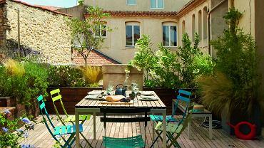 Rozległy taras wychodzi na patio. Krzesła Bistro (Fermob), drewniana zabudowa dla roślin i ławki to dzieło pana domu.