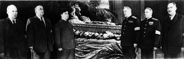 Po śmierci Stalina przy jego trumnie w Sali Kolumnowej Domu Rad wartę zaciągnęli członkowie Biura Politycznego partii. Pierwszy z lewej stoi Nikita Chruszczow, drugi ? Ławrientij Beria, który uważając się za następcę Wodza Narodów, wygłosił mowę nazwaną potem ''tronową''. Nie przypuszczał, że człowiek, którego ma po prawej ręce, wkrótce każe go rozstrzelać. Trzeci z lewej stoi Gieorgij Malenkow, a z drugiej strony trumny, od prawej: Łazar Kaganowicz, Kliment Woroszyłow i Nikołaj Bułganin.