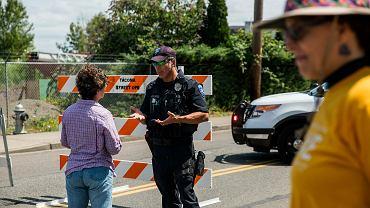 Oficer policji usiłuje przekonać szykujących się do demonstracji obywateli, by nie gromadzili się w okolicach ośrodka przetrzymywania imigrantów w Tacoma, 13 lipca 2019 r.