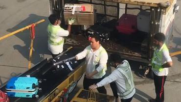 Bagaże pasażerów rzucane do wózka na lotnisku w Hongkongu