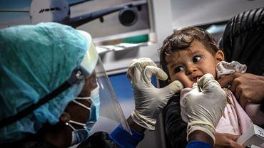 Pobieranie próbki do testu na koronawirusa od małego dziecka (zdjęcie ilustracyjne)