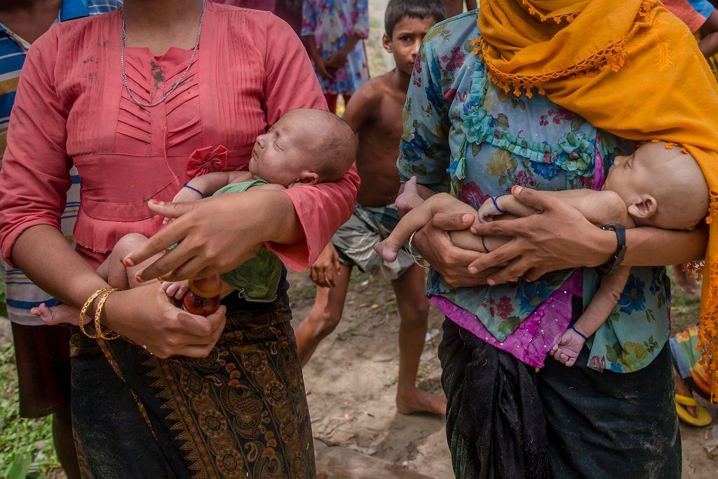 Dramat Rohindżów. Kobiety trzymają na rękach malutkie bliźnięta. To po prawej zmarło w trakcie ucieczki przed rzezią