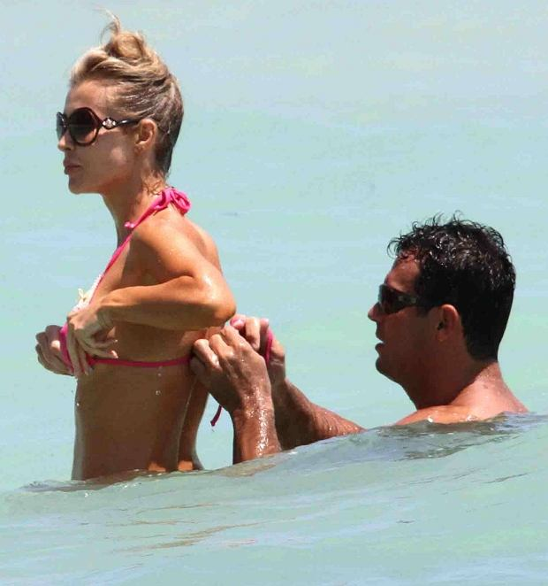 MAVRIXONLINE.COM - NO WEB/APPS/MOBILE UNLESS FEES AGREED - EXCLUSIVE!! Beautiful model, Joanna Krupa, is rescued by her fianc? Romain Zago when her pink bikini top came undone during a dip in the ocean. Zago helped her to do the bikini back up after she noticed the wardrobe malfunction which showed off her ample curves. Krupa, a one-time Dancing With the Stars alum, is currently starring on The Real Housewives of Miami. Miami Beach, FL. 20th April 2012  Fees must be agreed prior to publication.  Byline, credit, TV usage, web usage or linkback must read MAVRIXONLINE.COM.  Failure to byline correctly will incur double the agreed fee.  Tel: +1 305 542 9275.