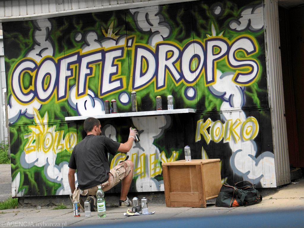 Łódź - grafficiarz maluje kiosk z dopalaczami