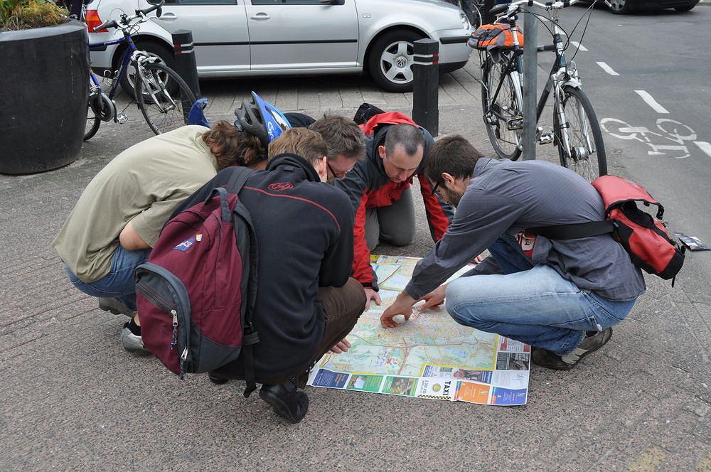 Grupa rowerzystów z Polski z pomocą mapy szuka właściwej drogi w Utrechcie.