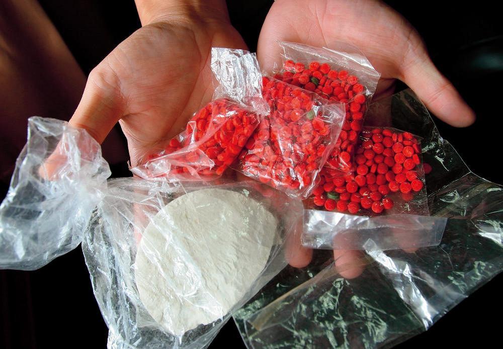 Narkotyki. Heroina (torebka z białym proszkiem) i metamfetamina (czerwone pigułki) przejęte podczas operacji przeciwnarkotykowej w Tajlandii