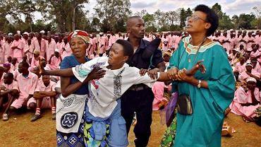 Rodzina i policja wyprowadzają kobietę, która przeżyła masakry w Rwandzie w 1994 r., ze stadionu w Butare, gdzie ponad dwa tysiące więźniów podejrzanych o udział w ludobójstwie zostało skonfrontowanych z niedoszłymi ofiarami we wrześniu 2002 r.